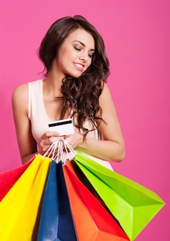 Attraktive frau, die einkaufstaschen und kreditkarte hält