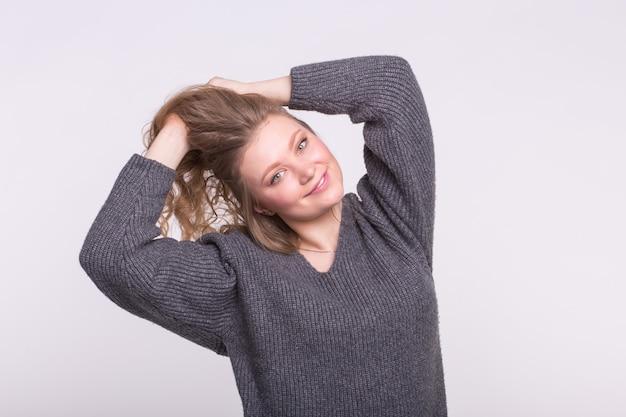 Attraktive frau, die ihr haar so glückliches und lustiges mädchen hält