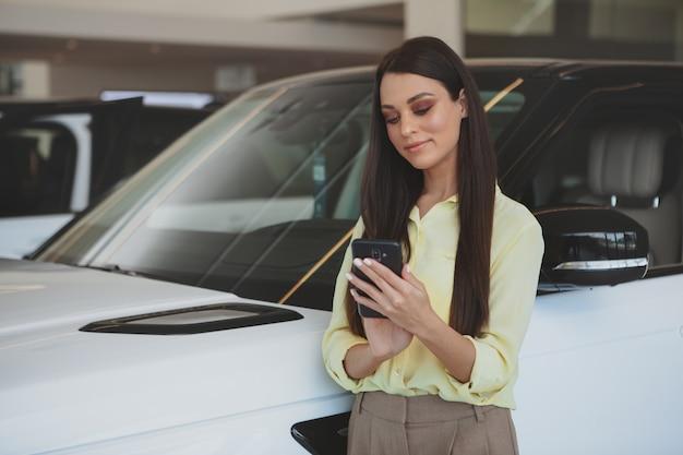 Attraktive frau, die ihr intelligentes telefon beim bying des neuwagens verwendet