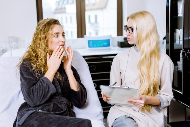 Attraktive frau, die ihre lippen und ihr gesicht zeigt, im kosmetikbüro sitzt und mit qualifizierter kosmetikerin spricht. professionelle kosmetikerin, die über hautprobleme der kundin spricht