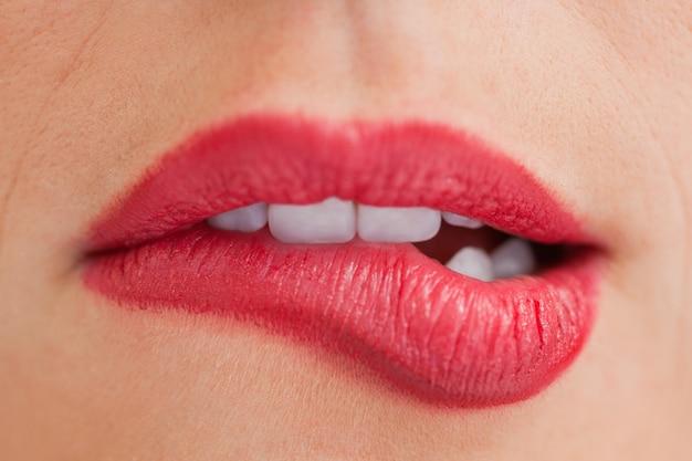 Attraktive frau, die ihre schönen lippen beißt
