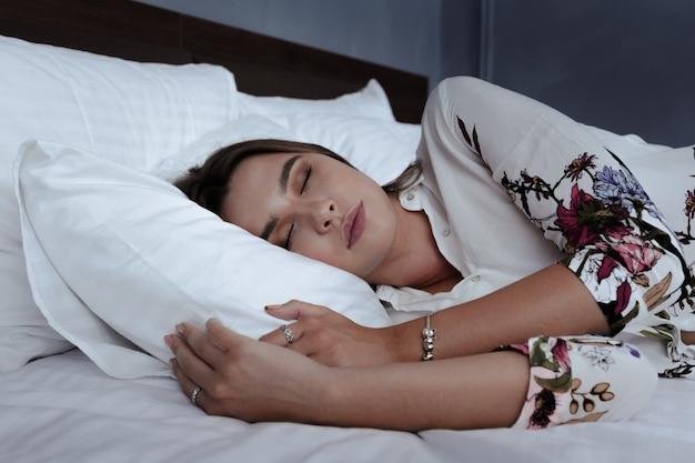 Attraktive frau, die im bett im hotelzimmer schläft
