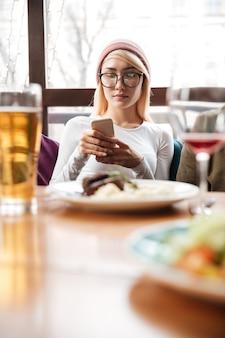 Attraktive frau, die im café sitzt, während handy benutzt