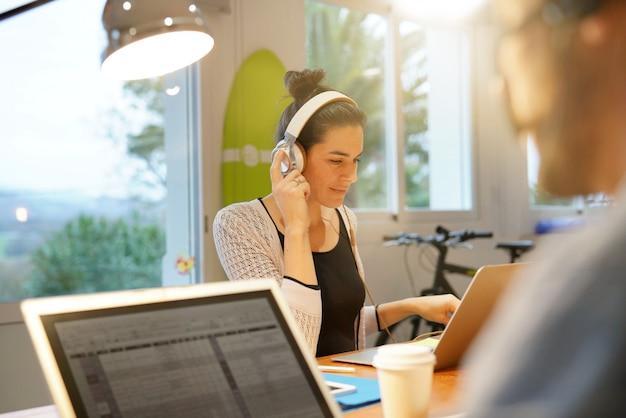Attraktive frau, die in co-arbeitsbüroräumen arbeitet