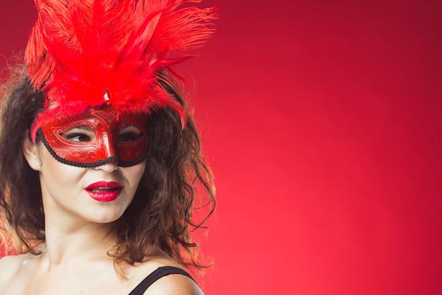 Attraktive frau, die in der roten maske aufwirft