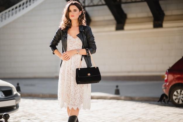 Attraktive frau, die in der straße im modischen outfit geht, geldbörse hält, nach unten schaut, schwarze lederjacke und weißes spitzenkleid tragend, frühlingsherbststil trägt