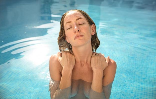 Attraktive frau, die in einem swimmingpool sich entspannt