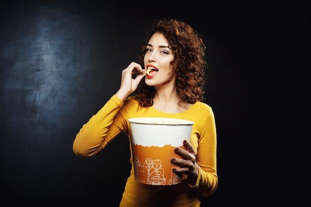 Attraktive frau, die käsiges popcorn isst, das erfreut und glücklich schaut