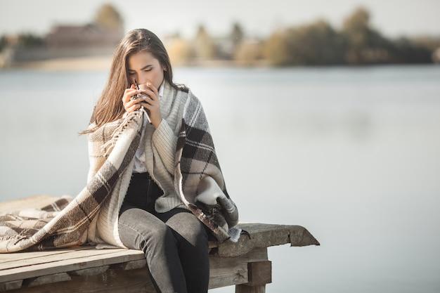 Attraktive frau, die kaffee oder tee am pier draußen trinkt