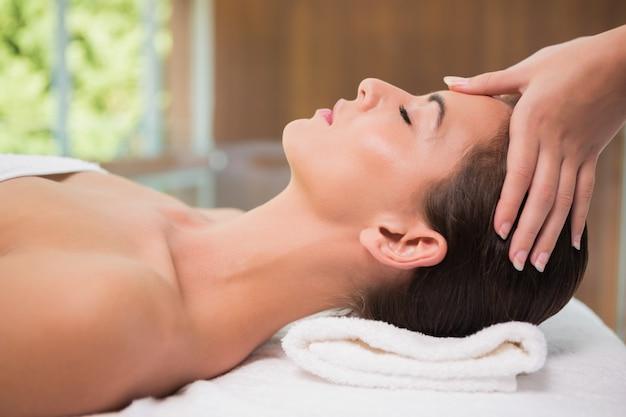 Attraktive frau, die kopfmassage in der badekurortmitte empfängt