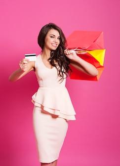 Attraktive frau, die kreditkarte zeigt und einkaufstaschen hält