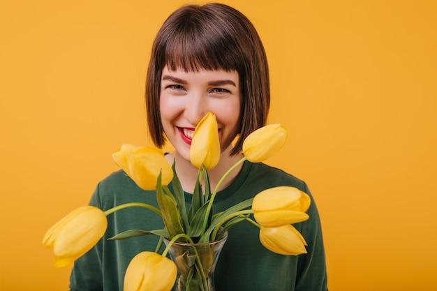 Attraktive frau, die lacht und blumen hält. porträt von hübschen brünetten mädchen, die glück mit tulpen ausdrücken.