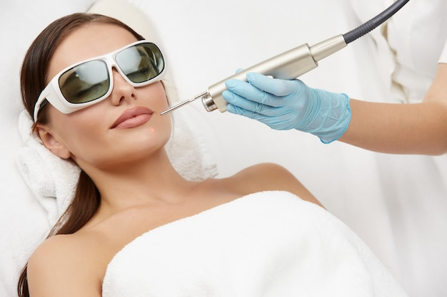 Attraktive frau, die laserverjüngung für ihr kinn im schönheitssalon erhält
