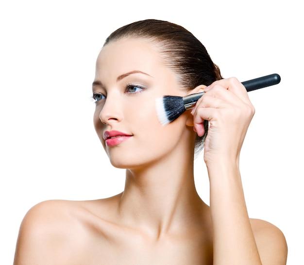 Attraktive frau, die make-up auf gesicht macht. modemodell, das auf weißem hintergrund aufwirft