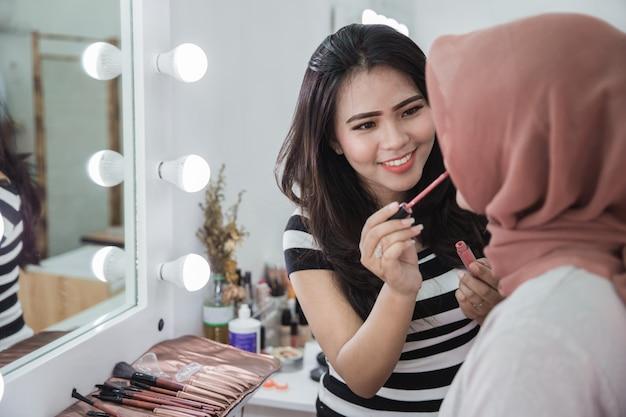 Attraktive frau, die make-up auf ihren freund aufträgt
