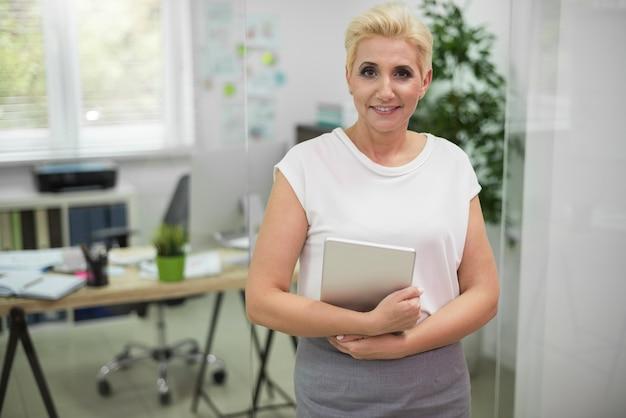Attraktive frau, die mit einem digitalen tablett aufwirft