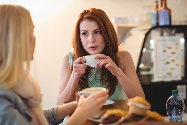 Attraktive frau, die mit freund am café spricht