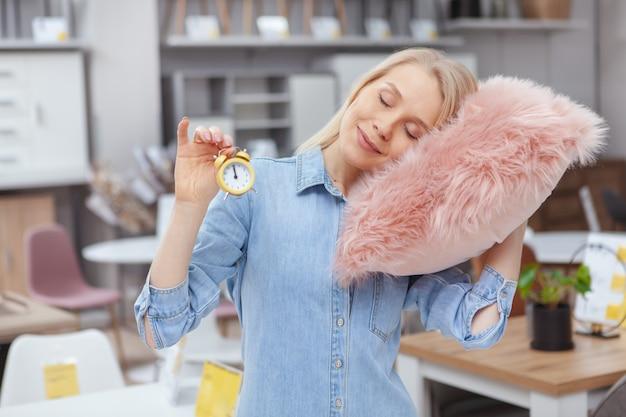 Attraktive frau, die mit geschlossenen augen lächelt, sich auf flauschigem rosa kissen entspannend, kleinen wecker haltend
