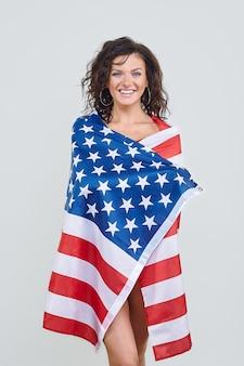 Attraktive frau, die mit usa-flagge auf weißem hintergrund aufwirft