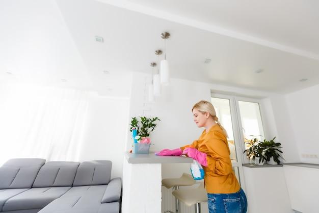 Attraktive frau, die möbel in der küche mit einem lappen säubert