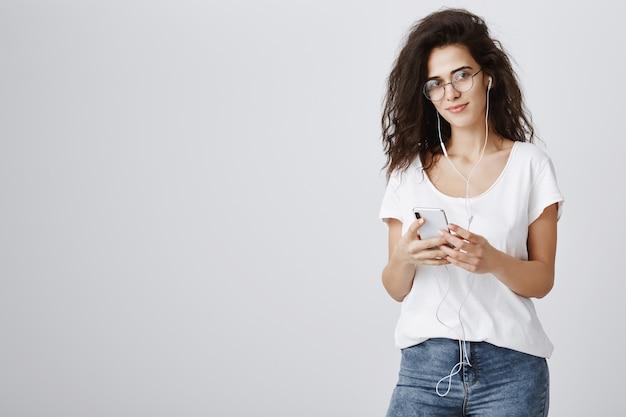 Attraktive frau, die musik in kopfhörern und nachrichten über mobiltelefon hört