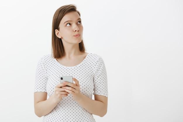 Attraktive frau, die nachdenkliche obere rechte ecke schaut, während sie denkt, wie auf nachricht zu antworten, handy hält