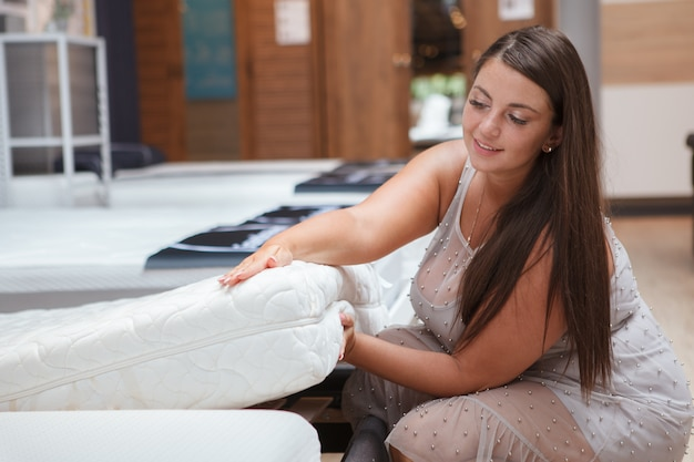 Attraktive frau, die orthopädische matratze im verkauf am möbelgeschäft untersucht