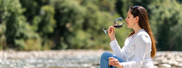 Attraktive frau, die rotwein sitzt auf einem felsen im flussufer trinkt. horizontales banner oder header.