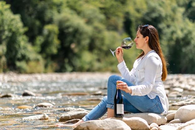 Attraktive frau, die rotwein sitzt auf einem felsen im flussufer trinkt.