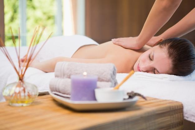 Attraktive frau, die rückenmassage in der badekurortmitte empfängt