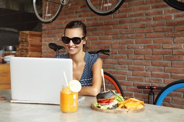 Attraktive frau, die schatten trägt, die vor offenem allgemeinem laptop sitzen und bildschirm mit glücklichem ausdruck betrachten, während videoanruf mit freund haben