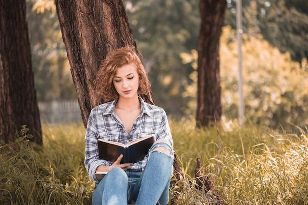Attraktive frau, die sich auf baum lehnt und garten des buches öffentlich liest