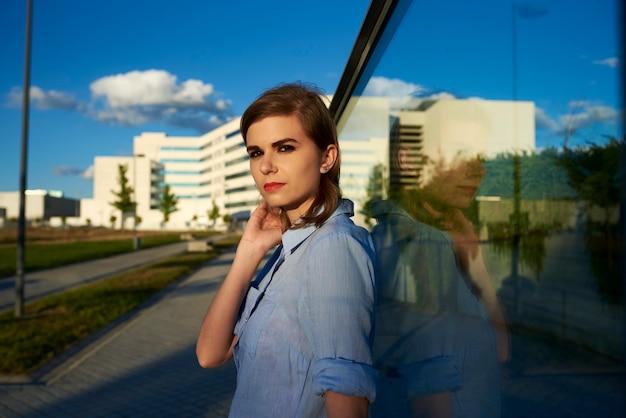 Attraktive frau, die sich auf ein glas stützt, ihr spiegelbild wird auf das glas projiziert. sie ist draußen in einem park.