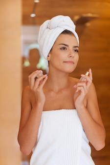 Attraktive frau, die sich parfüm nach dem duschen sprüht