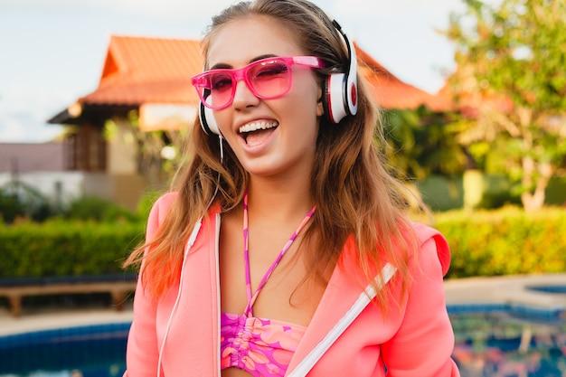 Attraktive frau, die sport am pool im bunten rosa kapuzenpulli trägt, der sonnenbrillen trägt, die musik in den kopfhörern in den sommerferien hören, tennis spielen, sportart