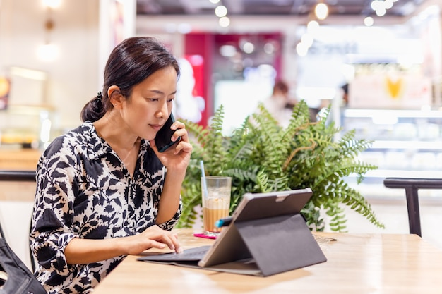 Attraktive frau, die telefoniert, während sie am laptop im café sitzt