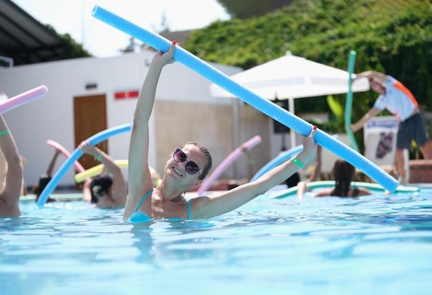 Attraktive frau, die übungen mit nudeln macht, beschäftigt sich mit aqua-aerobic