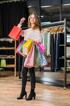 Attraktive frau, die unterschiedliche größe der papiertüte im butikenshop trägt