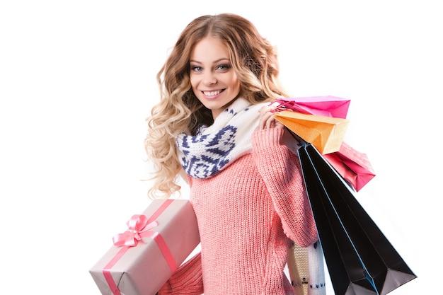Attraktive frau, die viele geschenkboxen und taschen auf weißem hintergrund hält.