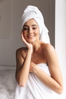 Attraktive frau, die weißes handtuch trägt, während im badezimmer nach dem duschen in der wohnung steht