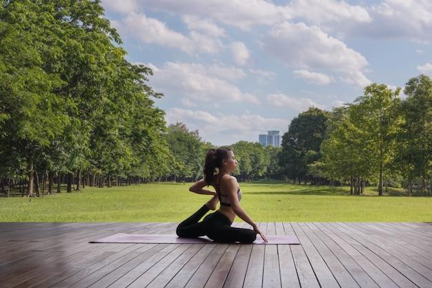 Attraktive frau, die yoga für ihre gute gesundheit spielt