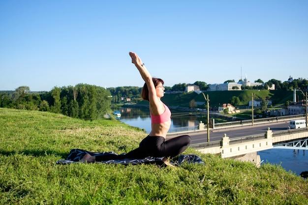 Attraktive frau, die yoga im freien praktiziert.
