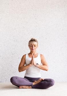 Attraktive frau, die zu hause yoga praktiziert