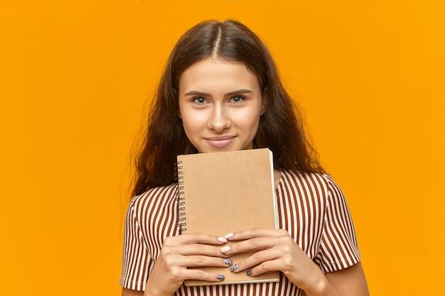 Attraktive frau eine studentin mit stilvoller maniküre, die kamera mit freudigem lächeln betrachtet