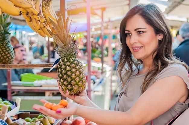 Attraktive frau einkaufen im grünen markt. closeup portrait schöne junge frau abholung, die wahl von früchten, ananas. positive gesichtsausdruck emotion gefühl gesund lebensstil