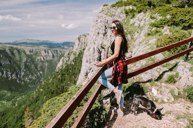 Attraktive frau entspannt sich in den bergen mit herrlicher aussicht. authentische lange haare alleinreisende
