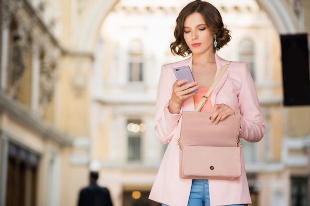 Attraktive frau gekleidet im trendigen outfit, das in straße geht
