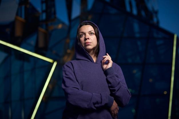Attraktive frau gekleidet in einen hoodie innenstadt in der stadt