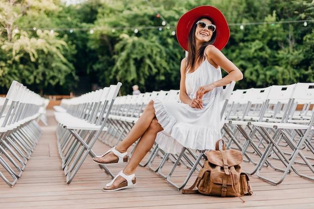 Attraktive frau gekleidet in weißem kleid, rotem hut, sonnenbrille, die im sommer freilufttheater allein auf stuhl sitzt, modetrend im frühlingsstraßenstil, accessoires, rucksack, soziale distanzierung