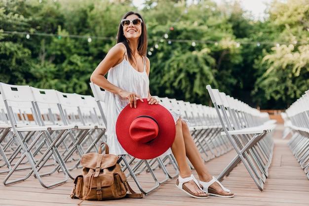 Attraktive frau gekleidet in weißem kleid, rotem hut, sonnenbrille, die im sommer freilufttheater auf stuhl allein sitzt, frühlingsstraßenart-modetrend, accessoires, reisen mit rucksack